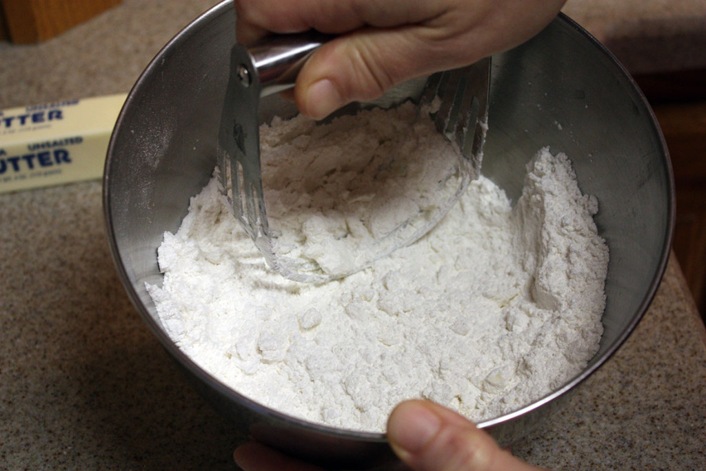 the butter being cut into the flour with a pastry blender