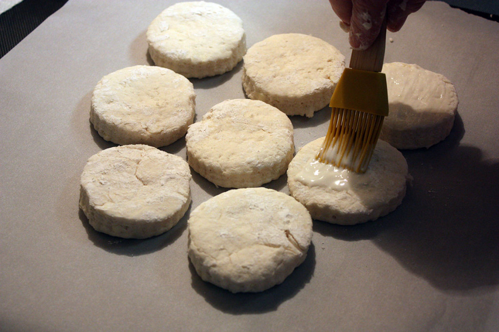 tops of the biscuits being brushed with buttermilk