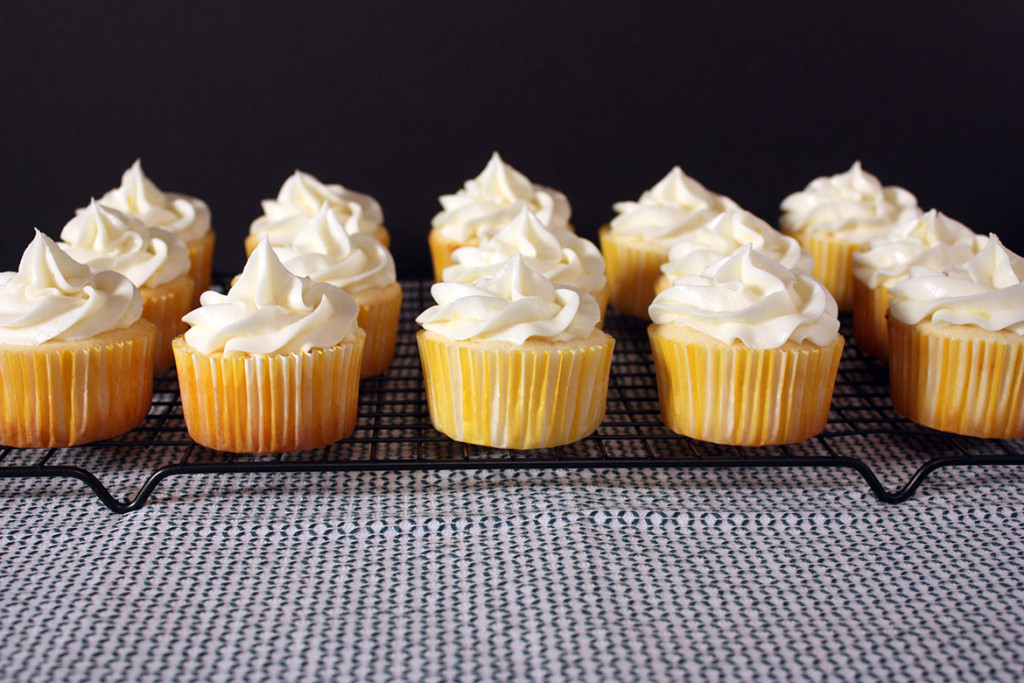 frosted Lemon Cupcakes lined up on a wire rack