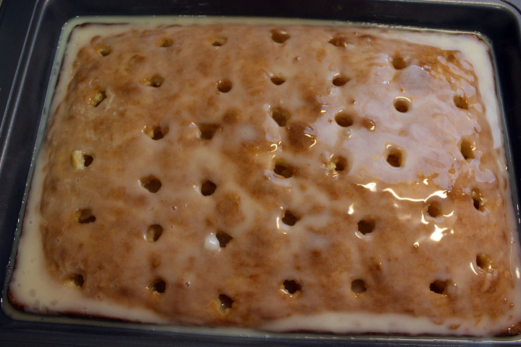 Coconut sheet cake with holes poked into it with the coconut cream mixture poured over