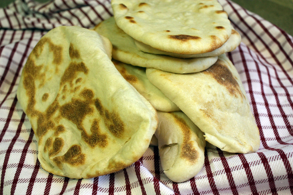 Naan Flatbread stacked on a red and white striped kitchen towel