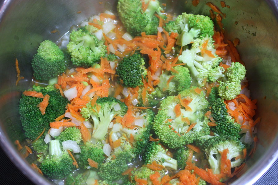 Broccoli, carrots, and onions in a pot
