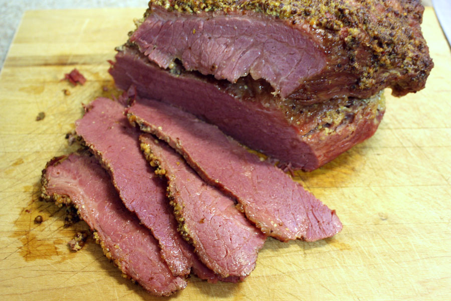 Corned Beef with Mustard Sauce sliced on a wooden cutting board