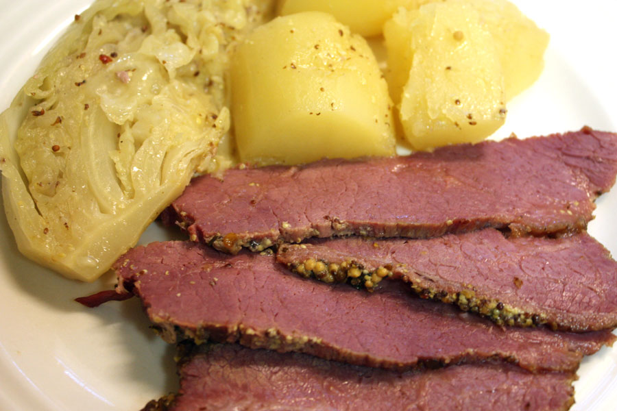 Corned Beef with Mustard Sauce on a white plate with potatoes and cabbage
