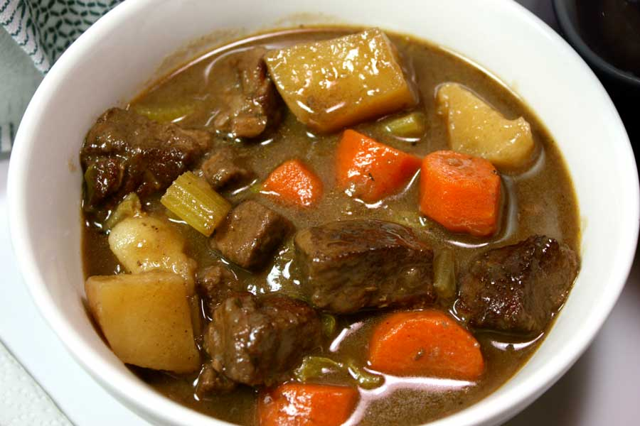hearty beef stew in white bowl