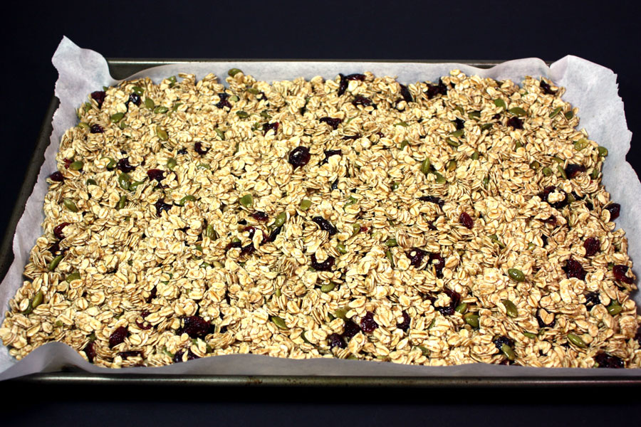 Granola pressed into a parchment paper lined baking pan