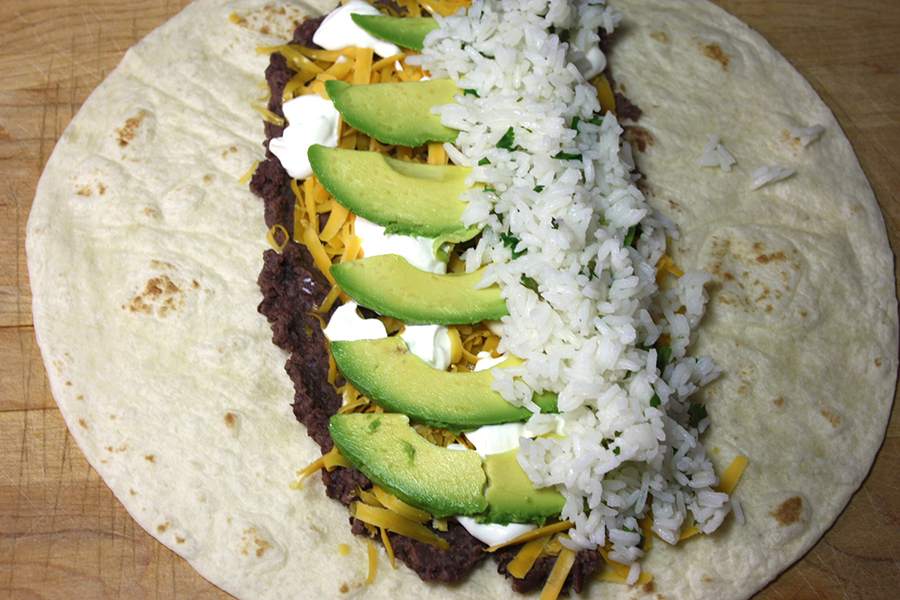 Vegetarian Burrito - flour tortilla on a wooden cutting board with the beans, cheese, sour cream, avocados, and rice placed in the center