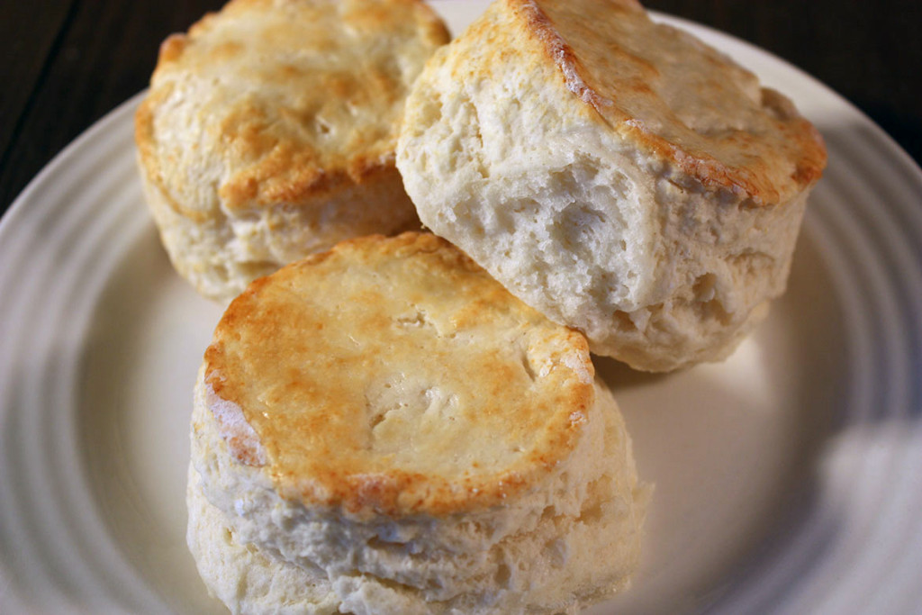Homemade Buttermilk Biscuits stacked on a white plate