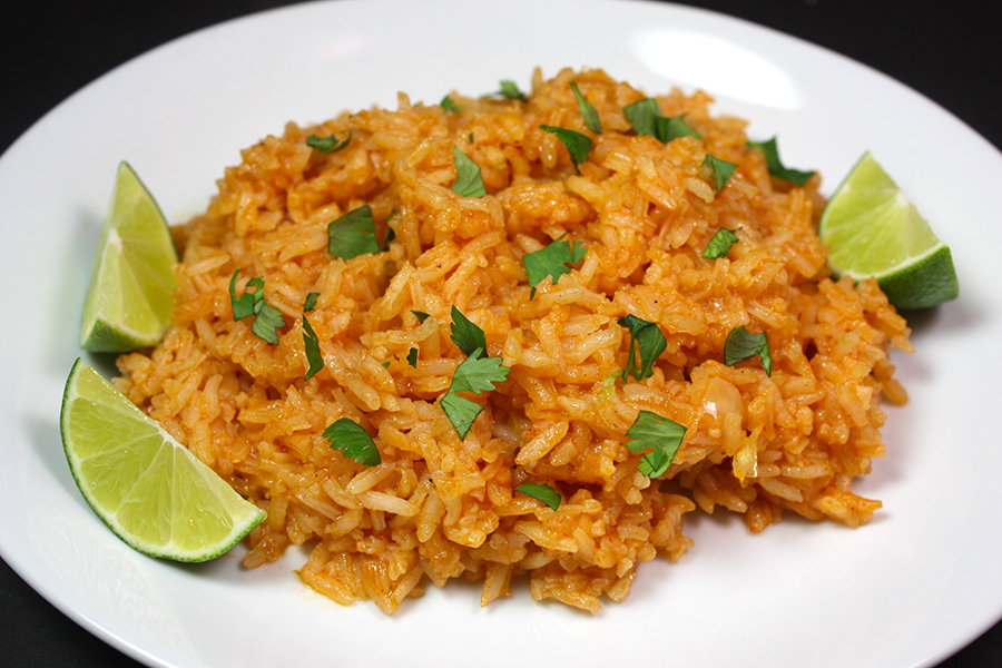 Mexican Rice on white plate garnished with cilantro and lime wedges