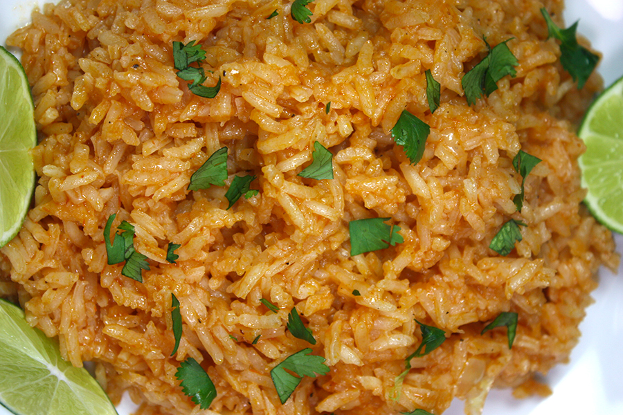 Mexican Rice on a white plate garnished with chopped parsley and lime wedges