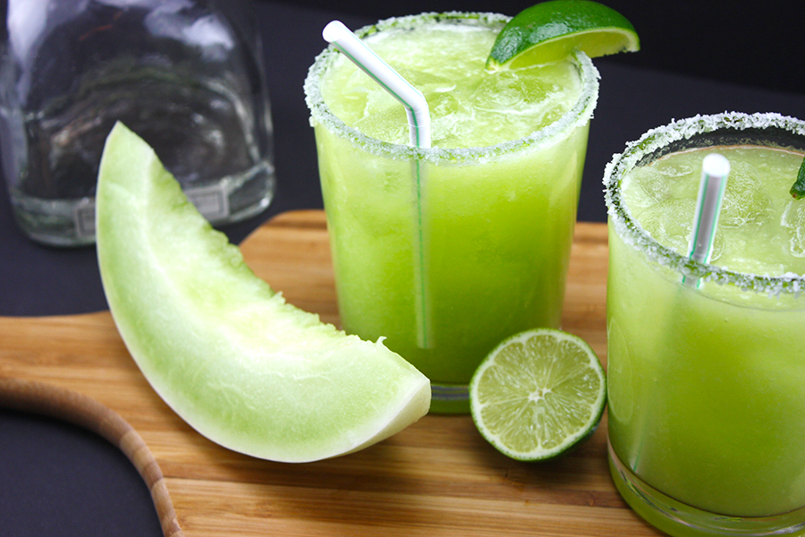 two honeydew margaritas in glasses garnished lime wedges on wooden board