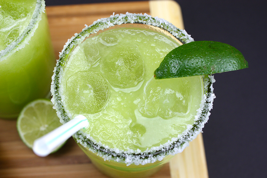 Honeydew Margaritas garnished with lime wedges on a wooden board