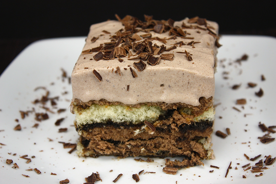 a slice of the Chocolate Tiramisu on a white plate garnished with chocolate shavings