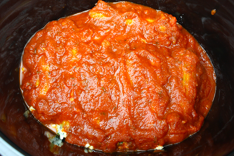 Spinach Ricotta Manicotti top with marinara sauce in the crock of a slow cooker