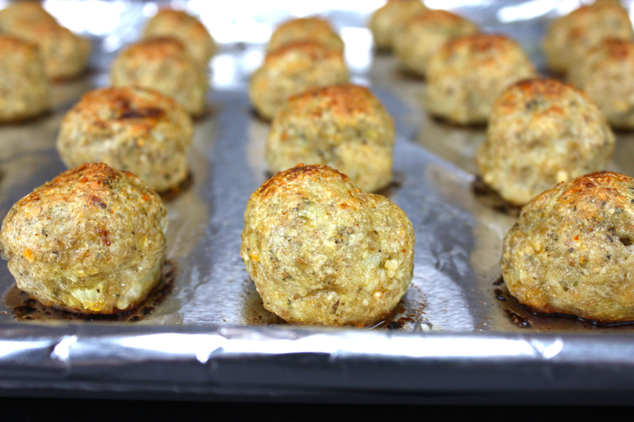 Chicken Parmesan Meatballs on a foil lined baking sheet