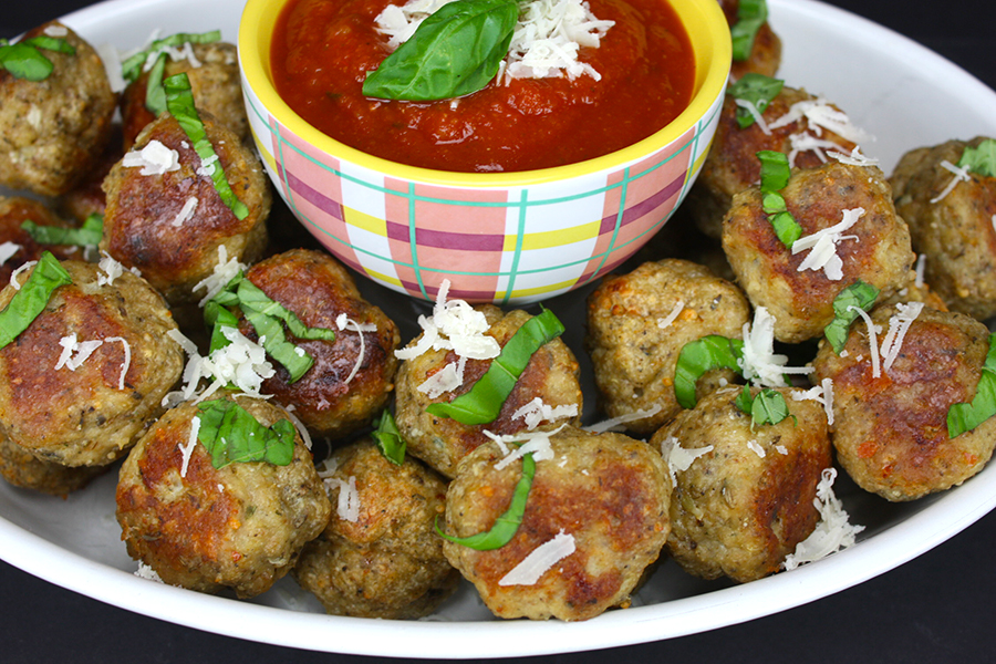 chicken Parmesan meatballs on a platter with marinara sauce in the middle
