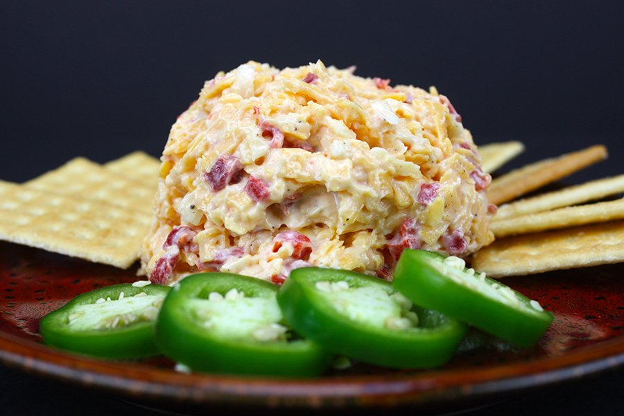 pimento cheese on red plate with crackers and fresh jalapeno slices