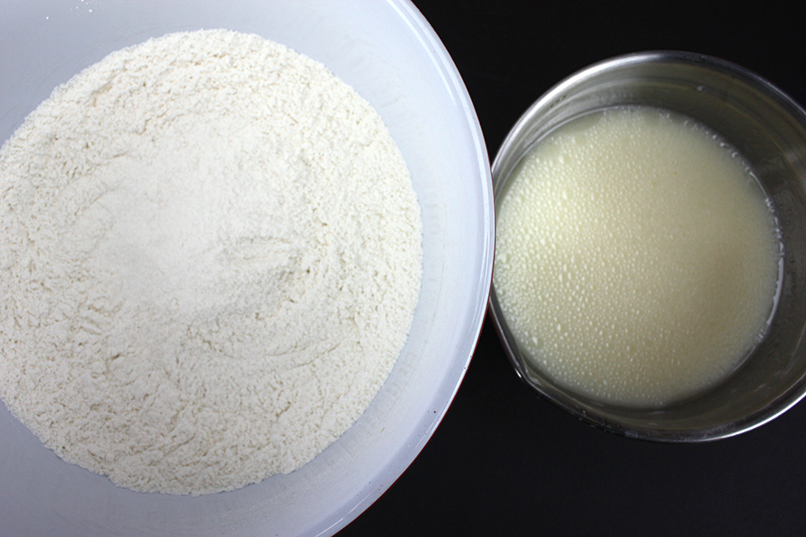 White Cake - dry ingredients combined in a white bowl and wet ingredients in a metal mixing bowl