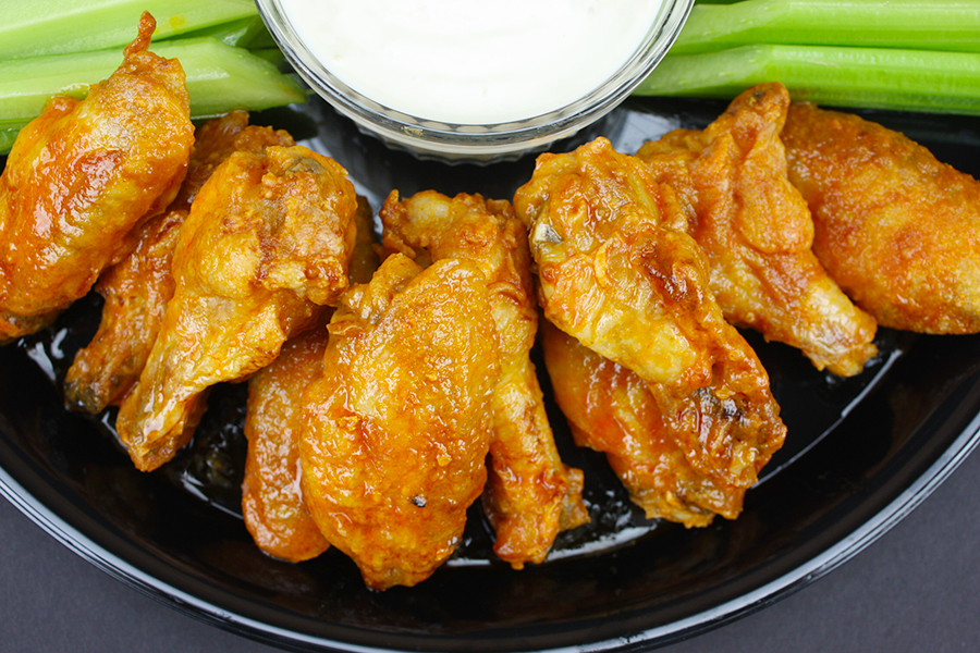 cripsy chicken wings on black platter with celery sticks and blue cheese dipping sauce