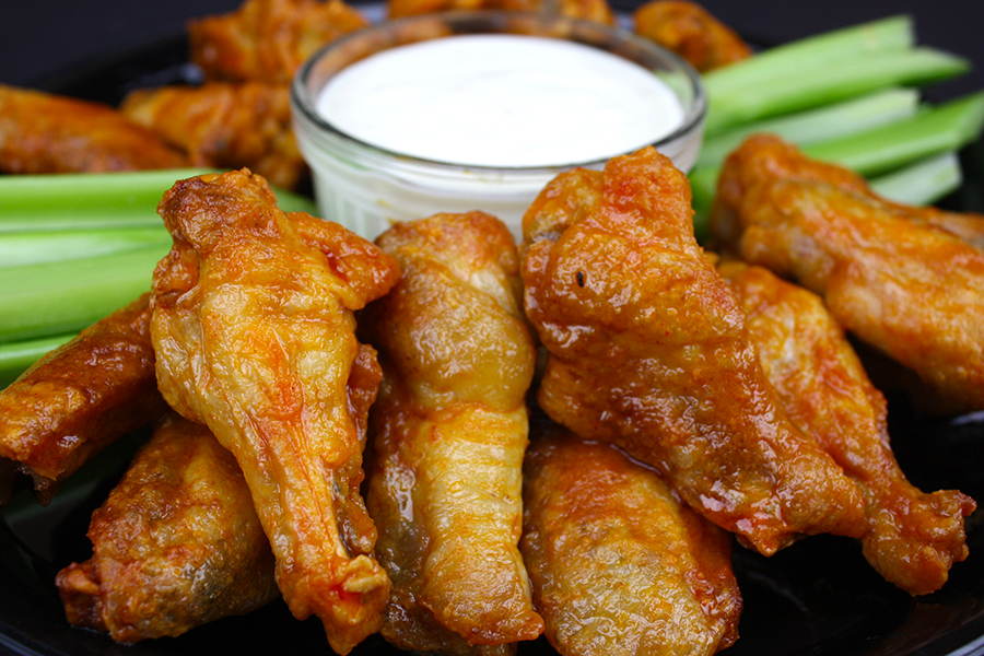 Crispy Oven Baked Chicken Wings on black platter with celery sticks and blue cheese dip