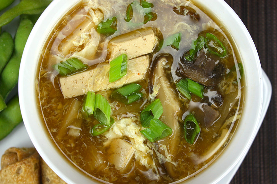 Hot and Sour Soup in white bowl garnished with chopped green onions