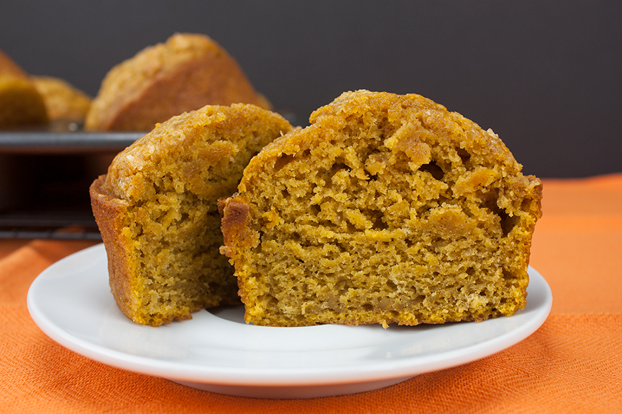 Bakery Style Pumpkin Muffin sliced in half on white plate