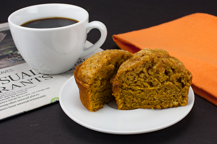 bakery style pumpkin muffin sliced in half on white plate with a cup of coffee in a white mug and a newspaper