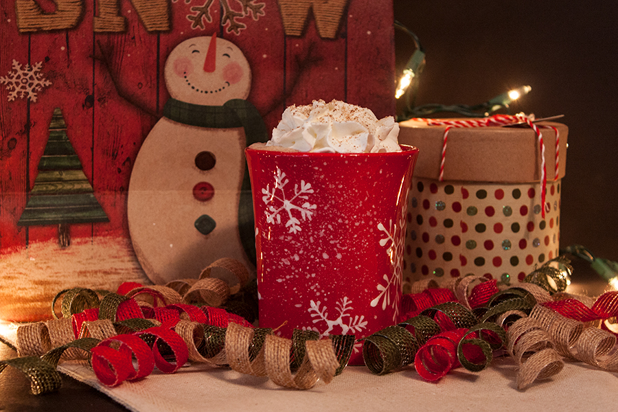 Eggnog Latte topped with whipped cream and grated nutmeg in a red coffee mug surrounded by ribbons and gift bags