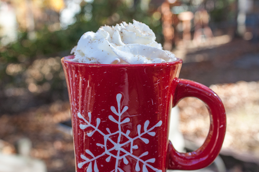 Eggnog Latte topped with whipped cream and grated nutmeg in a red coffee mug