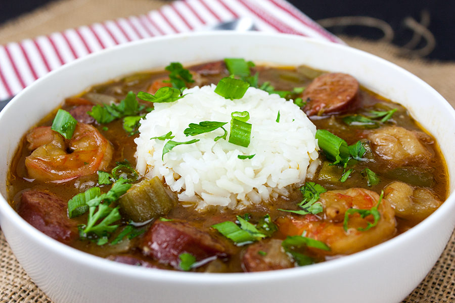 Shrimp and Sausage Gumbo in a white bowl with rice added to the middle and garnished with green onions and parsley