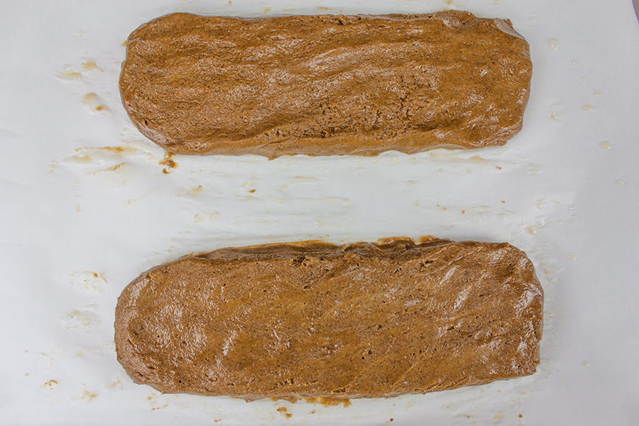 Gingerbread Biscotti dough formed into two logs on a parchment lined baking sheet