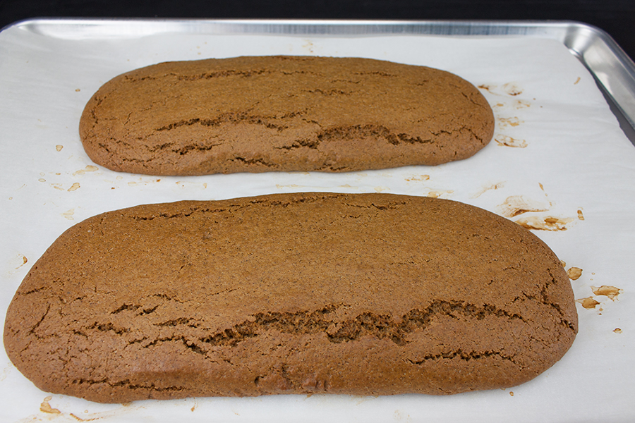 Gingerbread Biscotti dough logs baked on a parchment lined baking sheet