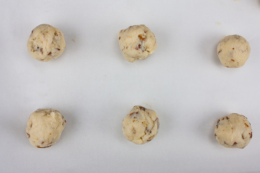 Italian Butterball Cookie dough balls on a parchment lined baking sheet