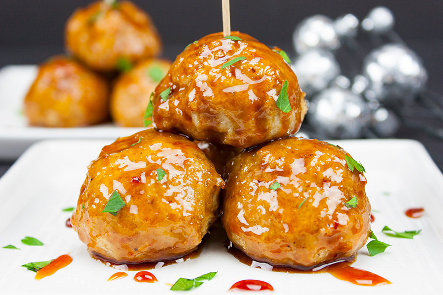 Firecracker Chicken Meatballs stacked on white plate drizzled with sauce
