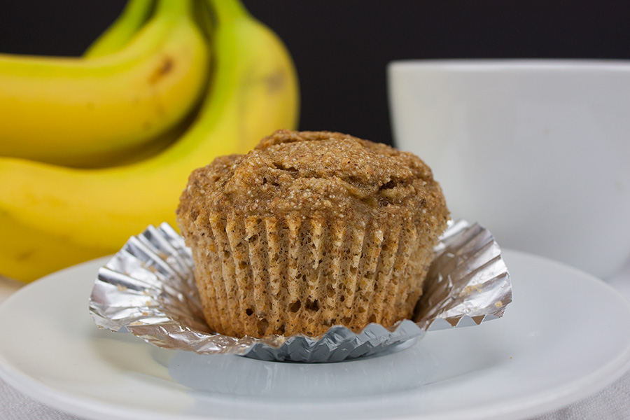 Healthy Whole Wheat Banana Muffin on white plate bananas in the background