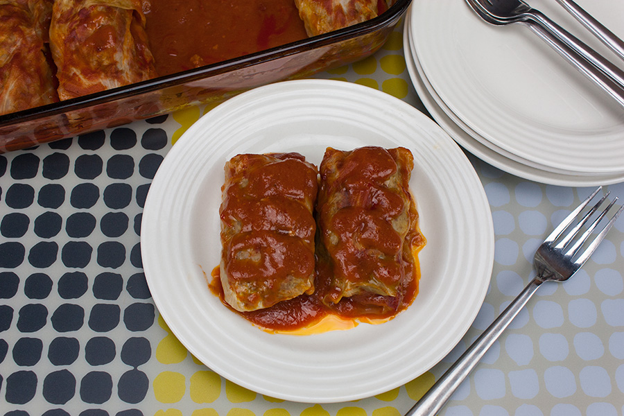 Easy Stuffed Cabbage Rolls - Tender leaves of cabbage stuffed and rolled with beef, garlic, onion, and rice, simmered in a rich tomato sauce.