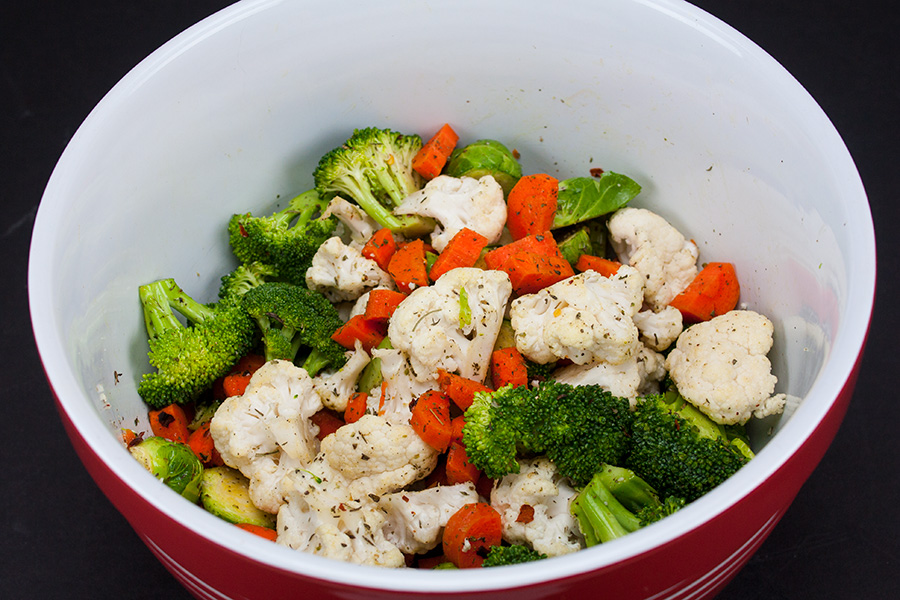 Sheet Pan Roasted Chicken and Vegetables - vegetables tossed with spices in a mixing bowl