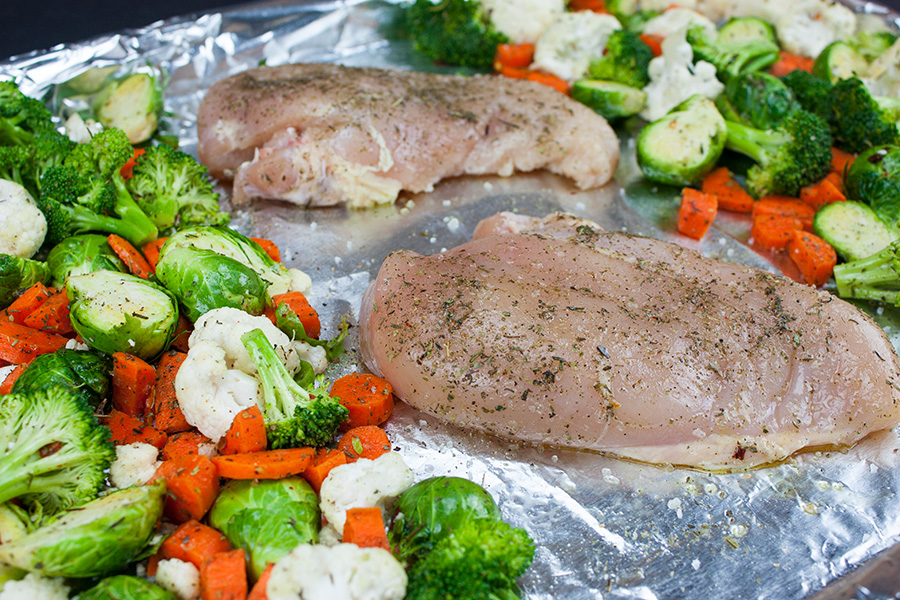Sheet Pan Roasted Chicken and Vegetables - raw vegetables and chicken breasts on a foil lined baking sheet