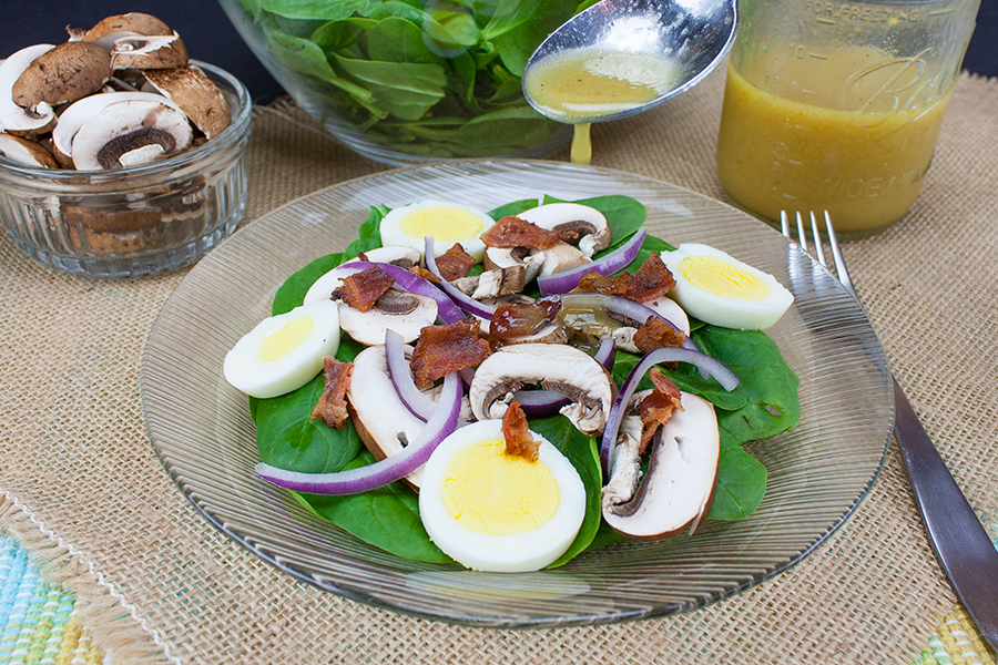 spinach salad in clear salad plate spoon of dressing pouring over