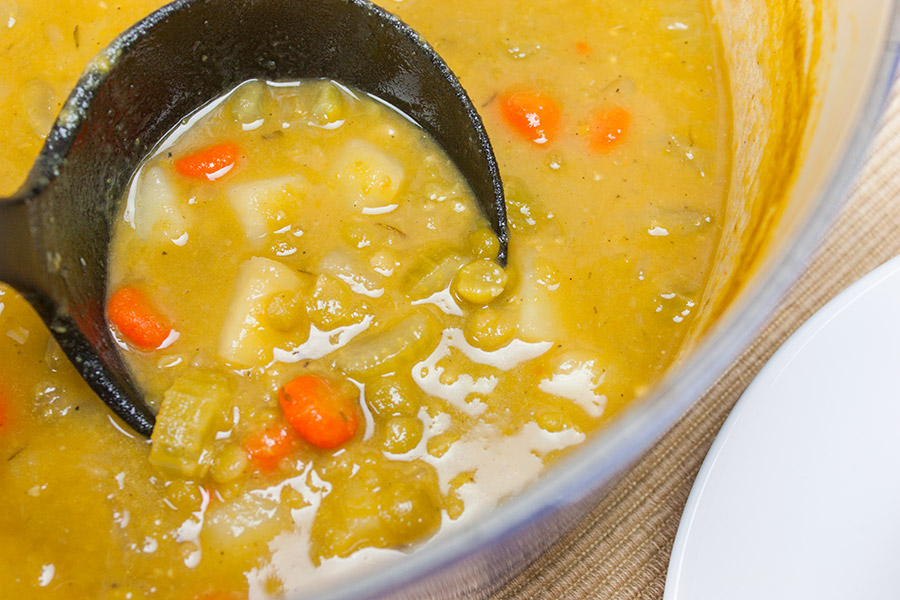 Vegan Split Pea Soup - a black ladle spooning out the soup