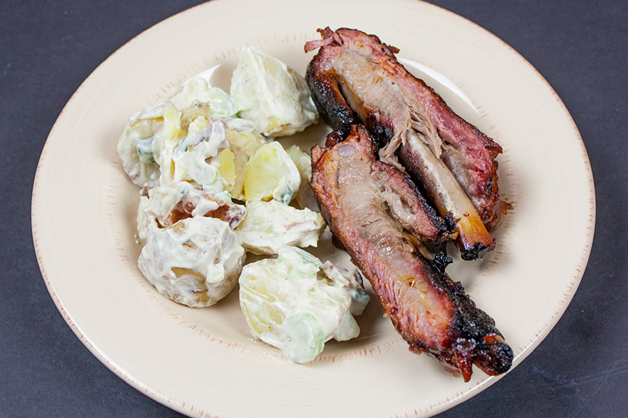 Bacon Potato Salad on a white plate with smoked ribs