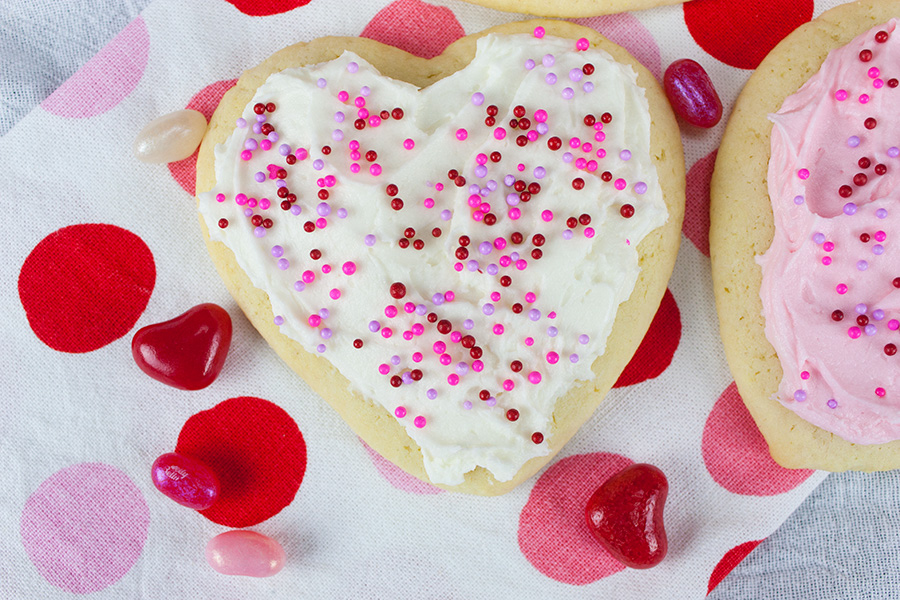 Soft Frosted Sugar Cookies on a pink and white polka dotted cloth