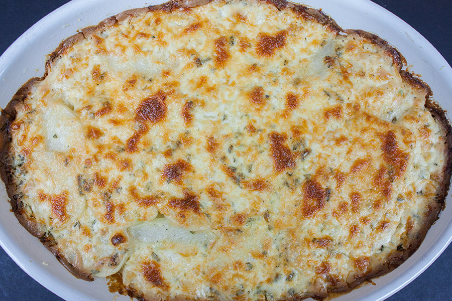 baked Creamy Herb Potatoes Gratin in an oval white casserole dish