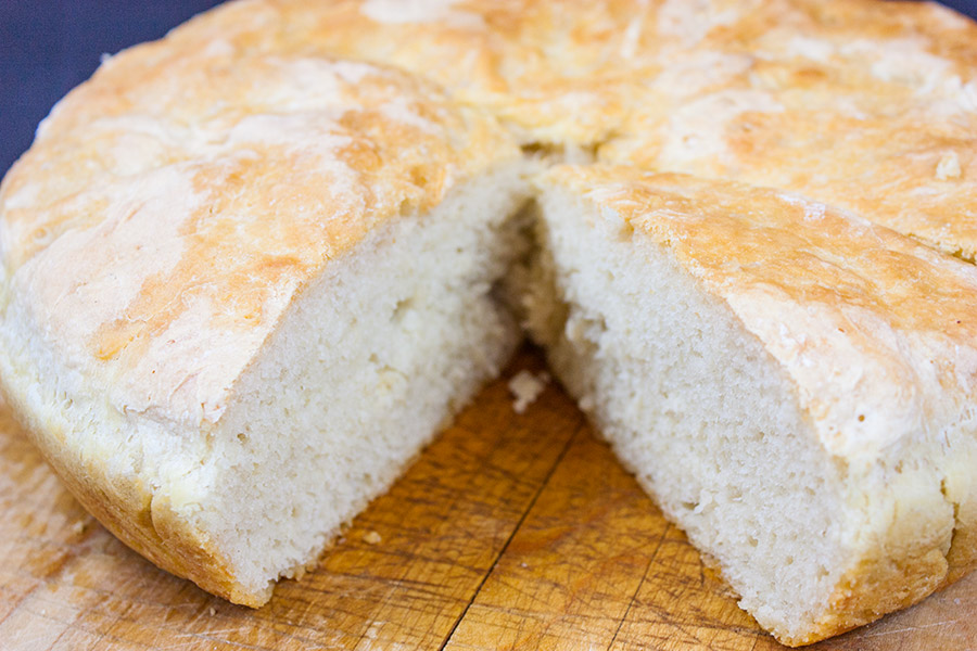 No Knead Skillet Bread sliced on a wooden cutting board