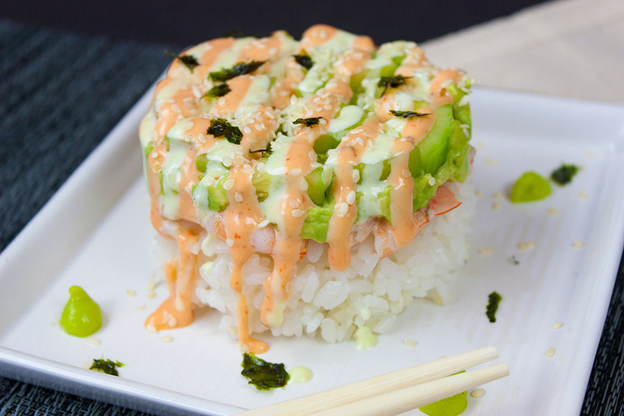 Spicy Shrimp Sushi Stack on white plate drizzled with sauce and dots of wasabi garnish