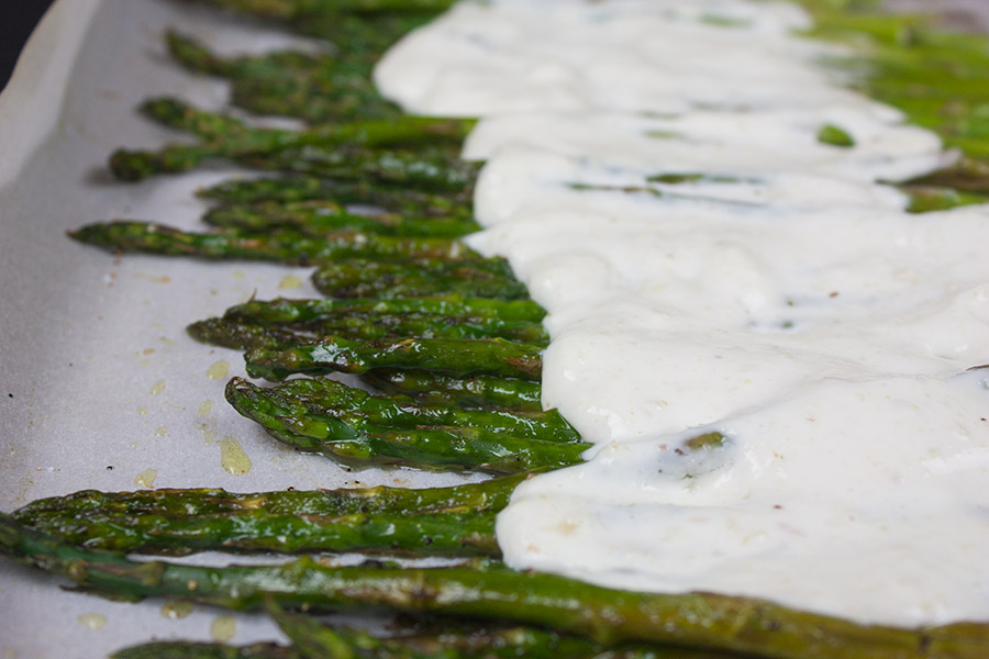 Roasted Asparagus with horseradish cream sauce poured over on the baking sheet