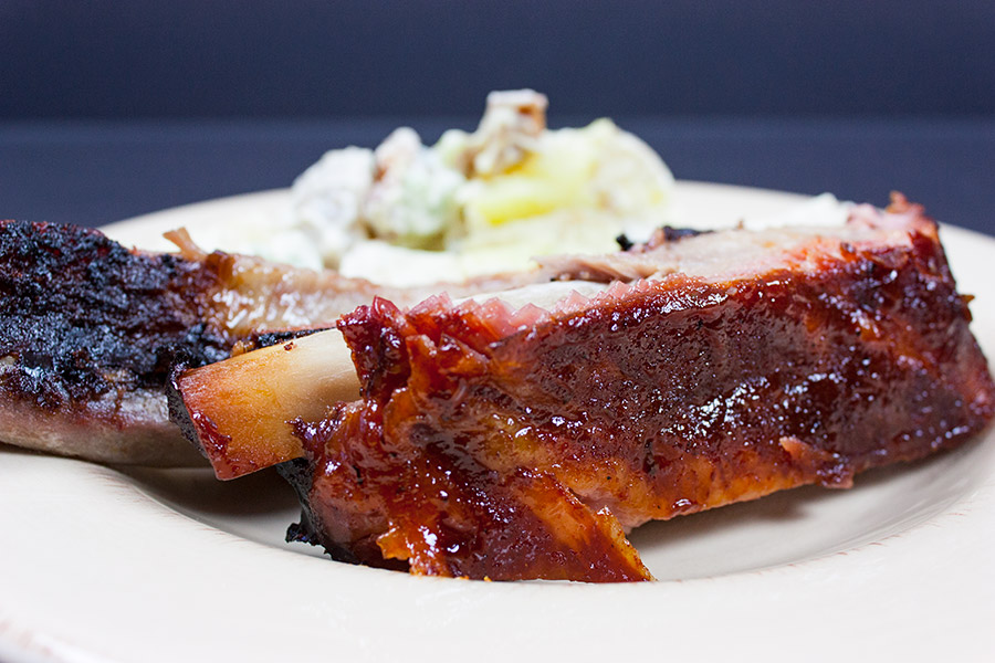 closeup of the St Louis Style Ribs on a plate with potato salad