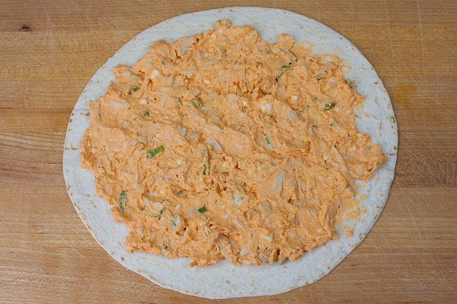 Buffalo Chicken mixture spread over flour tortilla