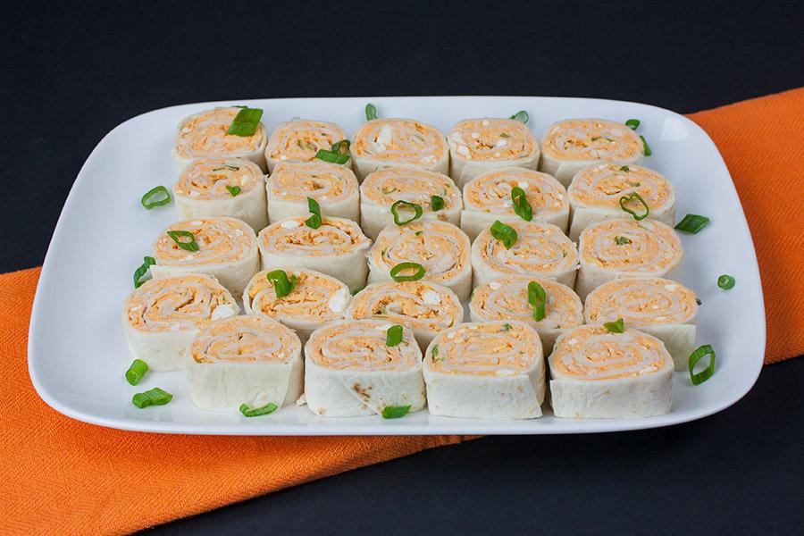 Buffalo Chicken Pinwheels on white platter garnished with green onions on orange cloth