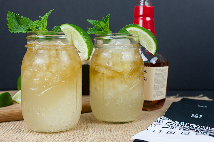 two Kentucky Mule drinks in mason jars garnished with mint and lime wedges